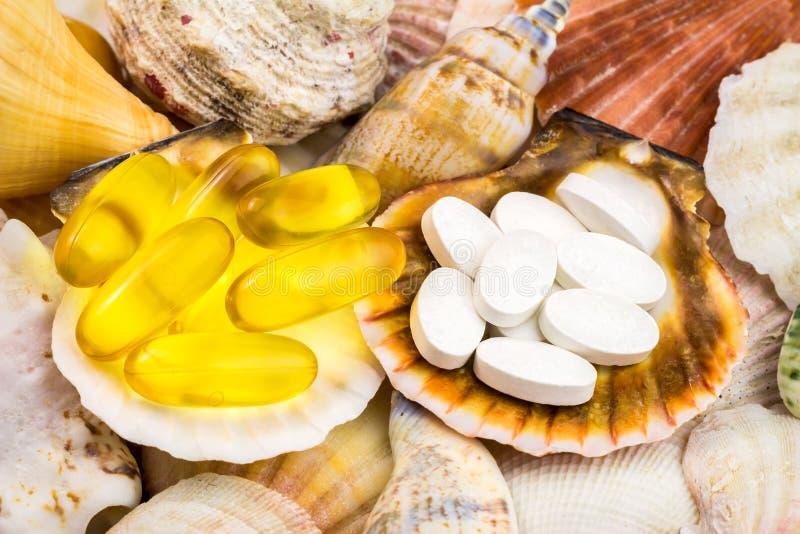 Χάπια ασβεστίου και ωμέγα 3 κάψες, φυσικό συμπλήρωμα τροφίμων στο όμορφο υπόβαθρο θαλασσινών κοχυλιών στοκ εικόνες