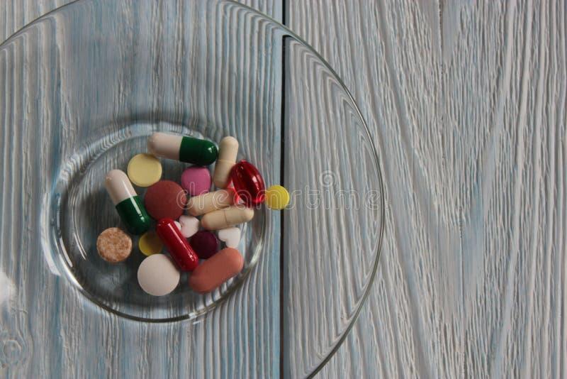 Χάπια, βιταμίνες και κάψες σε έναν γκρίζο ξύλινο πίνακα στοκ φωτογραφία με δικαίωμα ελεύθερης χρήσης