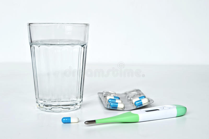 Χάπια, θερμόμετρο και ποτήρι του ύδατος στοκ φωτογραφία με δικαίωμα ελεύθερης χρήσης