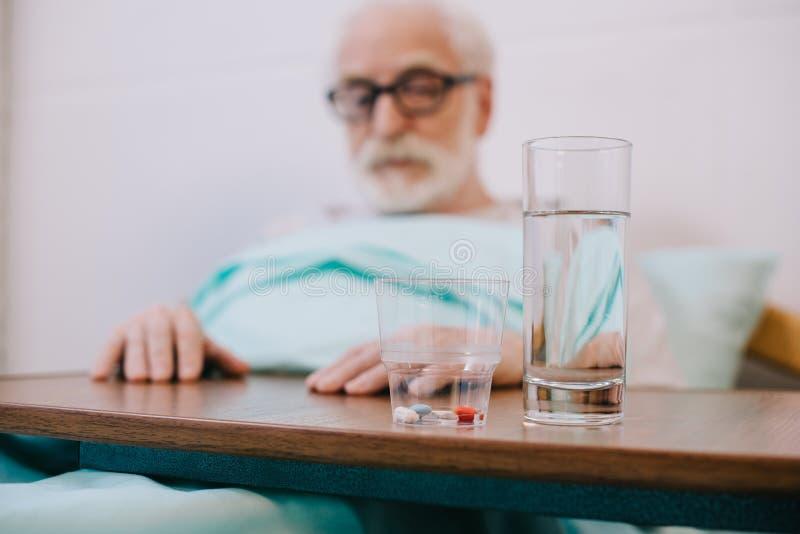 Χάπια και ποτήρι του νερού μπροστά από το ανώτερο άτομο στοκ φωτογραφίες