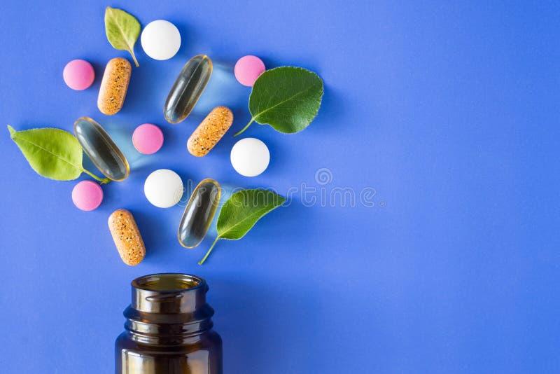 Χάπια που ανατρέπονται από ένα βάζο που αναμιγνύεται με τα φύλλα σε ένα μπλε υπόβαθρο στοκ εικόνα