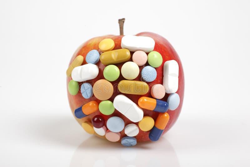 Χάπια στο μήλο στο άσπρο υπόβαθρο που συμβολίζει τη χημική μόλυνση των τροφίμων στοκ εικόνα με δικαίωμα ελεύθερης χρήσης