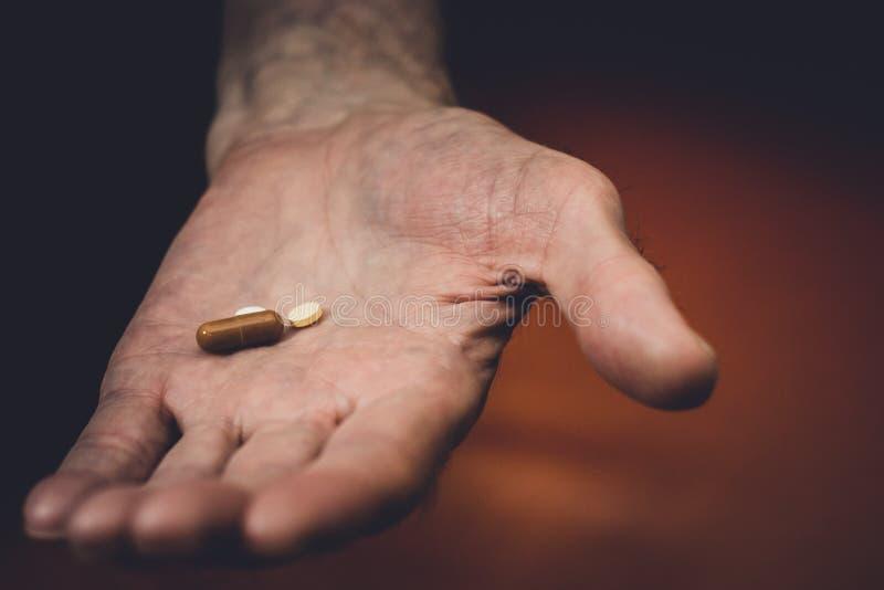 Χάπια στο παλαιό χέρι στοκ εικόνες με δικαίωμα ελεύθερης χρήσης