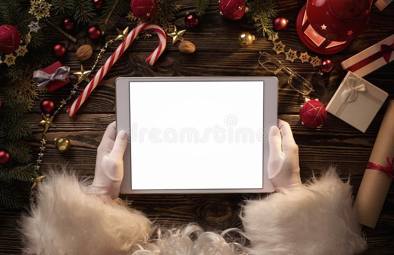 Χέρια Άγιου Βασίλη που κρατούν την κενή ψηφιακή ταμπλέτα στοκ φωτογραφία