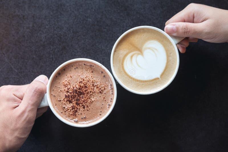 Χέρια ανδρών και γυναικών ` s που κρατούν τον καφέ και τα καυτά φλυτζάνια σοκολάτας με το ξύλινο επιτραπέζιο υπόβαθρο στοκ εικόνες με δικαίωμα ελεύθερης χρήσης