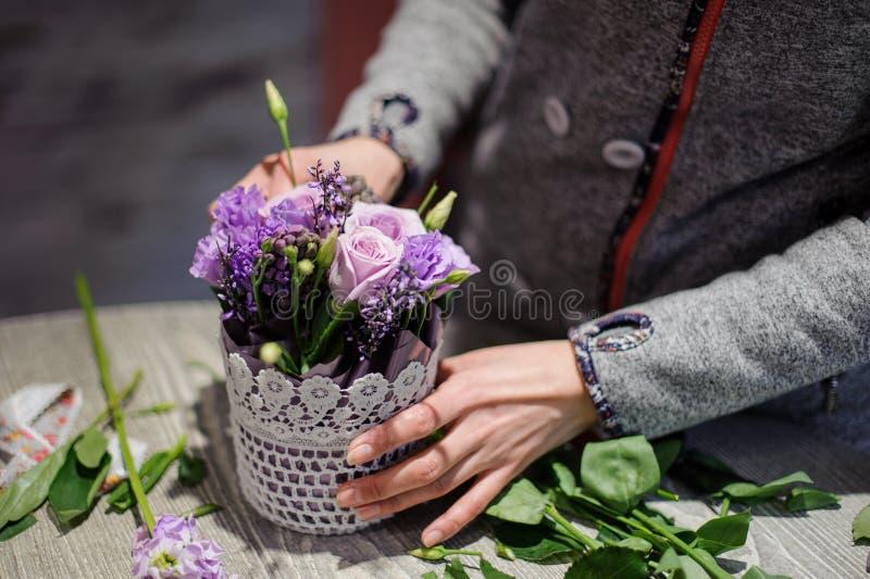 Χέρια ανθοκόμων που κάνουν μια αρκετά ιώδη ανθοδέσμη των λουλουδιών στοκ εικόνες