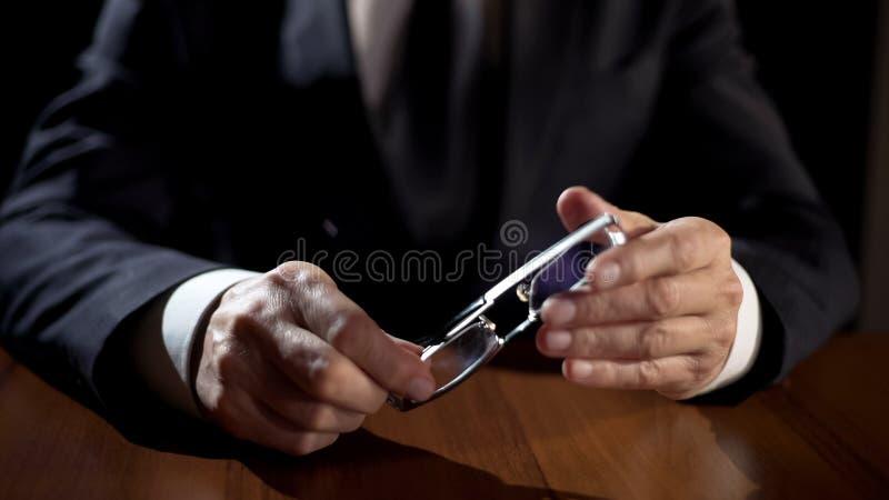 Χέρια αρσενικά eyeglasses εκμετάλλευσης ανακριτών, ρωτώντας ύποπτος εγκλήματος στοκ φωτογραφία με δικαίωμα ελεύθερης χρήσης