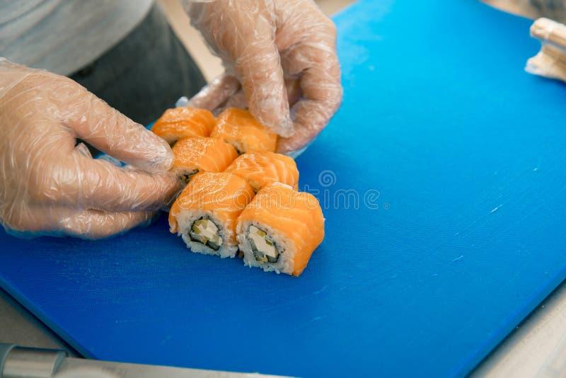 Χέρια αρχιμαγείρων που βάζουν τα σούσια Μάγειρας στα γάντια που τοποθετεί τους εύγευστους ρόλους σουσιών στο μαύρο πιάτο στοκ εικόνα