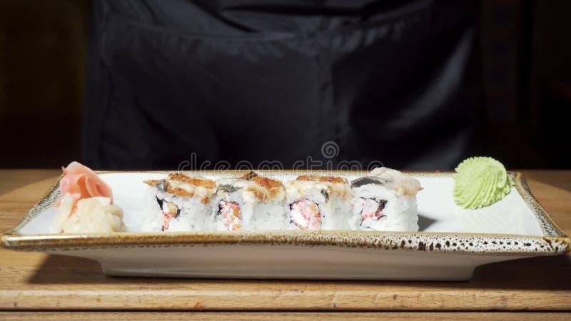 Χέρια αρχιμαγείρων που βάζουν τα σούσια στο πιάτο με το έτοιμες wasabi και την πιπερόριζα, ιαπωνική έννοια εστιατορίων τροφίμων Π στοκ φωτογραφία με δικαίωμα ελεύθερης χρήσης