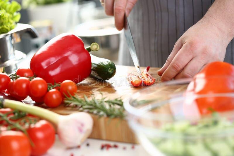 Χέρια αρχιμαγείρων που κόβουν το κόκκινο - καυτά μισά πιπεριών τσίλι στοκ φωτογραφία