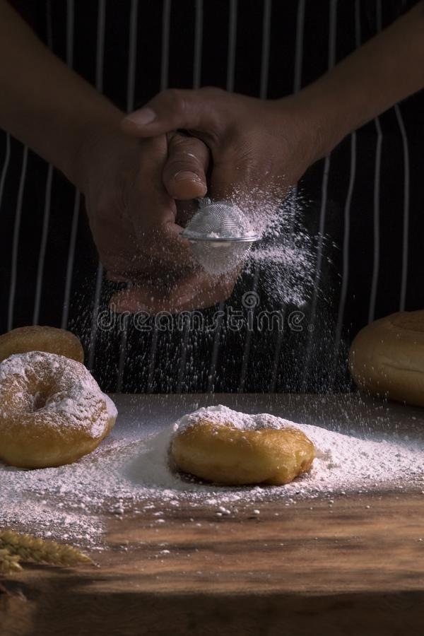 Χέρια αρχιμαγείρων ` s που ψεκάζουν τα γλυκά donuts με τη ζάχαρη και το αλεύρι τήξης στοκ εικόνες με δικαίωμα ελεύθερης χρήσης