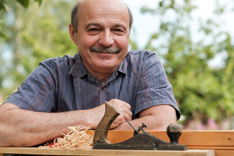 Χέρια ατόμων με το αεροπλάνο ξυλουργών ` s στο ξύλινο υπόβαθρο στοκ εικόνες