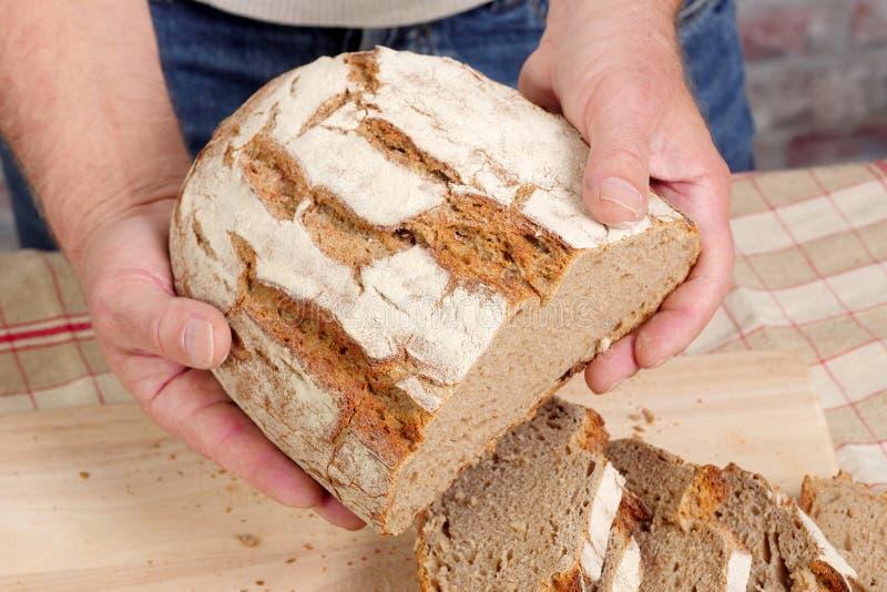 Χέρια ατόμων με το φρέσκο ψωμί στον ξύλινο πίνακα στοκ φωτογραφία