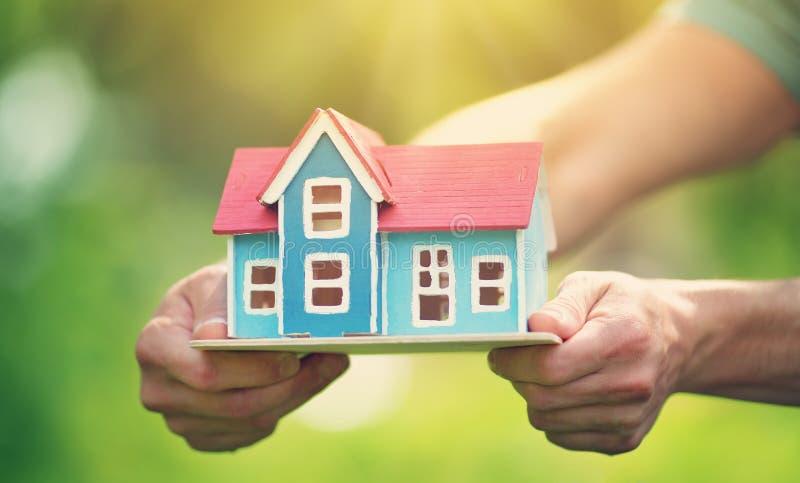 Χέρια ατόμων που κρατούν το ξύλινο σπίτι στοκ φωτογραφία με δικαίωμα ελεύθερης χρήσης