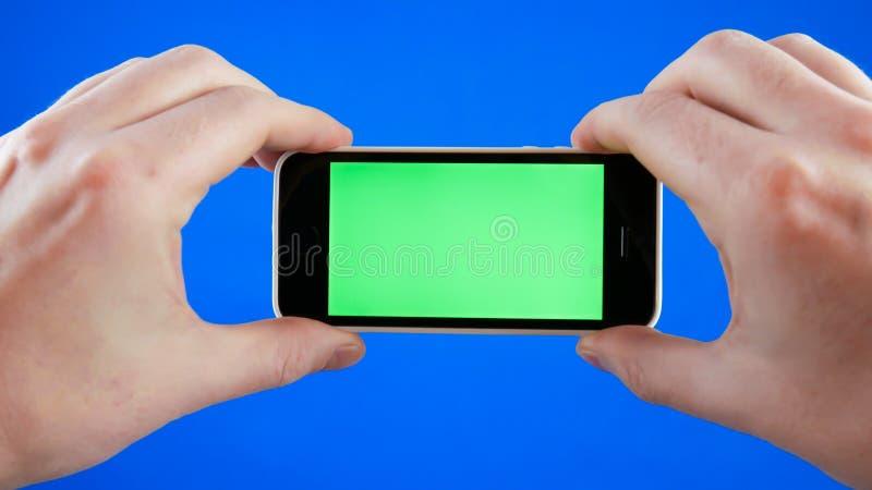 Χέρια ατόμων που κρατούν το smartphone σε μια οριζόντια θέση Πράσινη οθόνη στο τηλέφωνο και το μπλε chromakey Κανένα στοκ φωτογραφία με δικαίωμα ελεύθερης χρήσης