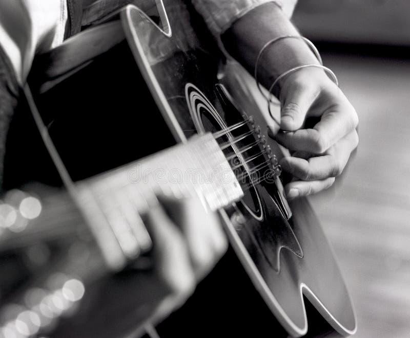 Χέρια ατόμων ` s κινηματογραφήσεων σε πρώτο πλάνο, δάχτυλα, που γρατζουνούν την ακουστική κιθάρα με την επιλογή στοκ εικόνα με δικαίωμα ελεύθερης χρήσης
