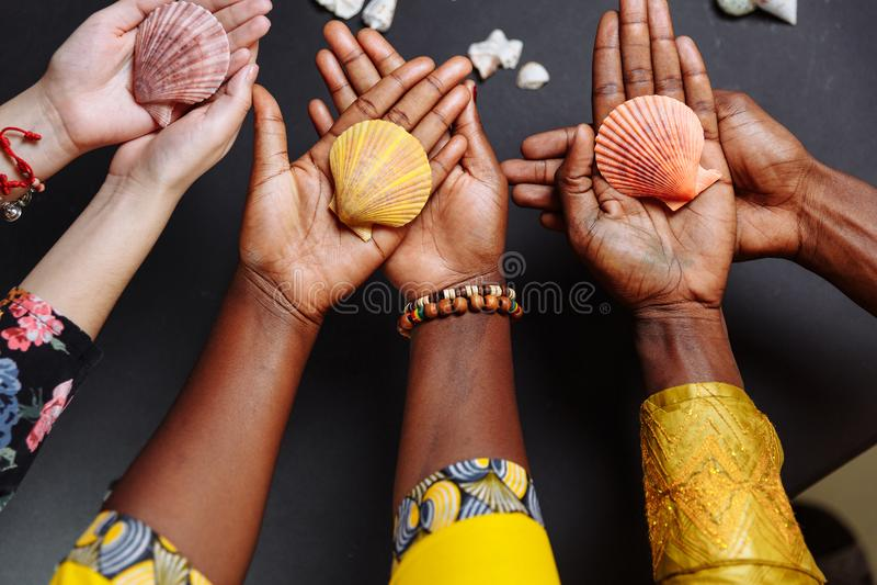 Χέρια Αφρικανών με παραδοσιακά ρούχα κρατώντας κοχύλια στοκ εικόνες