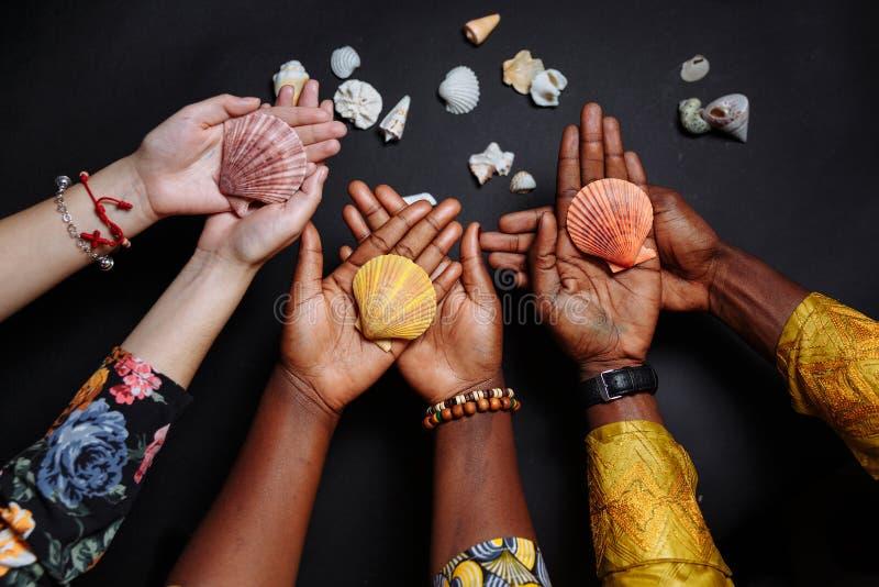 Χέρια Αφρικανών με παραδοσιακά ρούχα κρατώντας κοχύλια στοκ φωτογραφίες