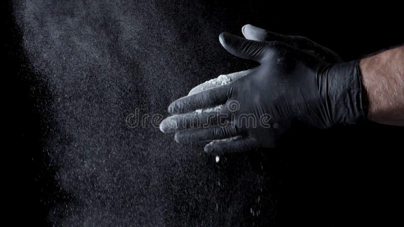 Χέρια βαμβακιού με το αλεύρι στο μαύρο υπόβαθρο Πλαίσιο Αρχιμάγειρας που χτυπά τα χέρια που καλύπτονται στο αλεύρι στοκ φωτογραφία