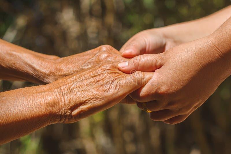 Χέρια βοηθείας, προσοχή για την ηλικιωμένη έννοια στοκ εικόνα