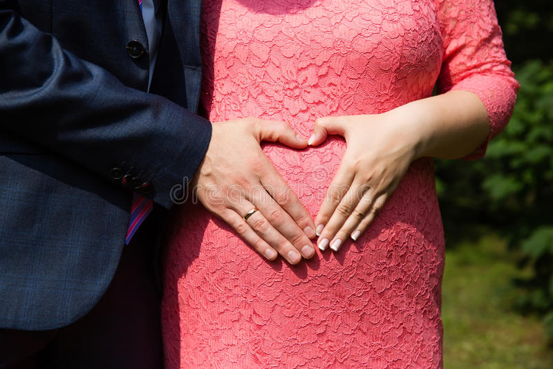Χέρια γαμήλιων ζευγών με τα δαχτυλίδια στην έγκυο κοιλιά της γυναίκας στοκ εικόνες
