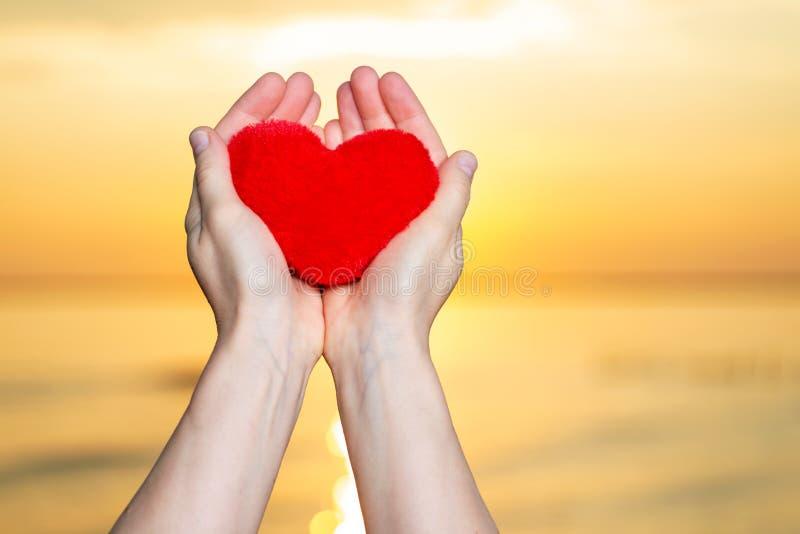 Χέρια γυναίκας που κρατούν την κόκκινη χνουδωτή καρδιά βελούδου στην ανατολή μπροστά από τη λίμνη Αγάπη, ειδύλλιο και φιλία στοκ φωτογραφία με δικαίωμα ελεύθερης χρήσης