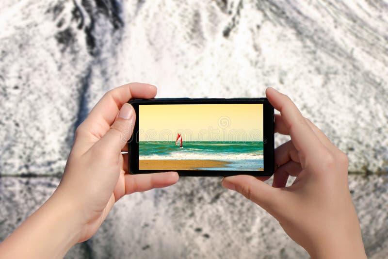 Χέρια γυναίκας που παίρνουν την εικόνα στο κινητό τηλέφωνο της θερινής παραλίας στο χιονώδες υπόβαθρο βουνών στοκ εικόνες