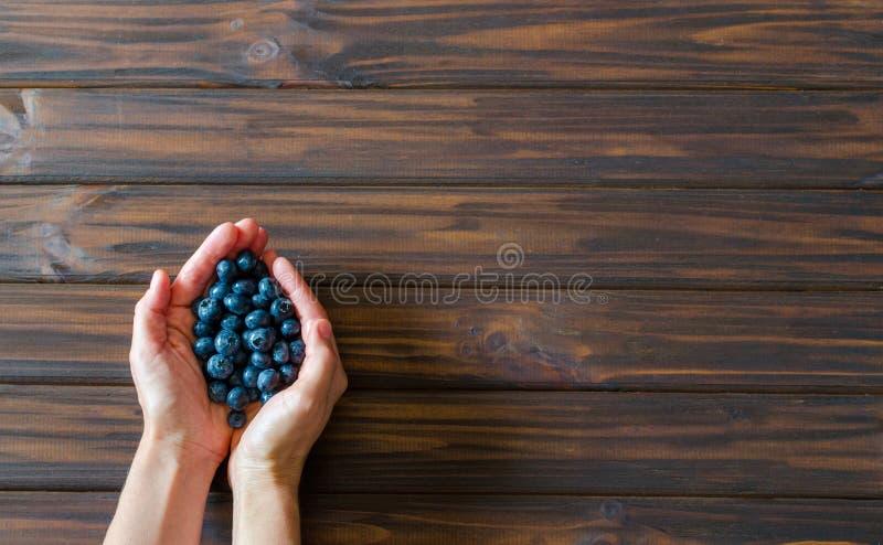 Χέρια γυναικών με τα βακκίνια στο σκοτεινό ξύλινο υπόβαθρο γραφείων r r backfill στοκ εικόνες