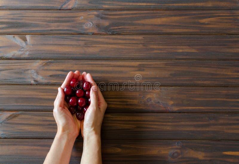 Χέρια γυναικών με τα κόκκινα κεράσια στο σκοτεινό ξύλινο υπόβαθρο γραφείων r r backfill στοκ φωτογραφίες
