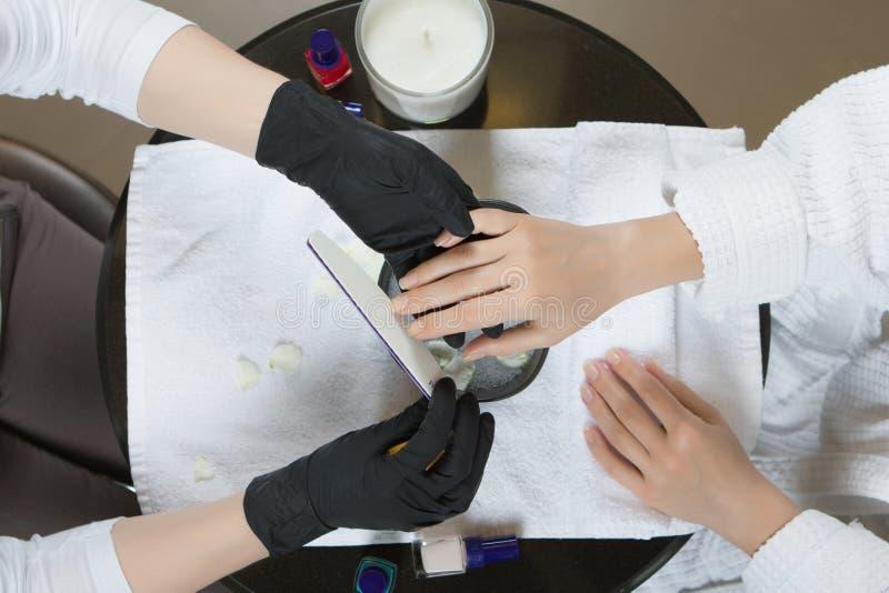 Χέρια γυναικών που λαμβάνουν το μανικιούρ και τη διαδικασία προσοχής καρφιών κοντά επάνω στοκ εικόνα με δικαίωμα ελεύθερης χρήσης