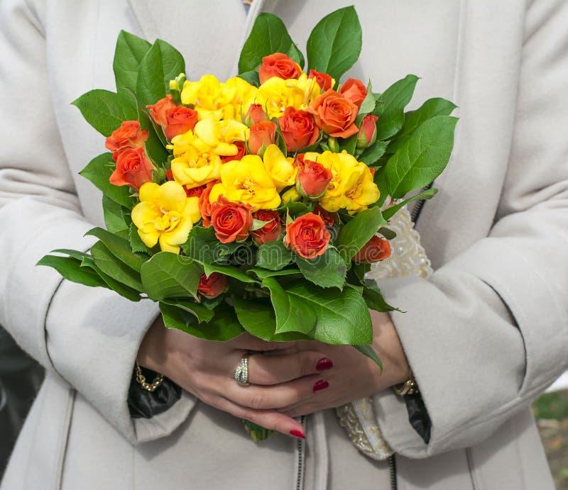 Χέρια γυναικών που κρατούν μια ανθοδέσμη των φυσικών λουλουδιών στοκ εικόνα