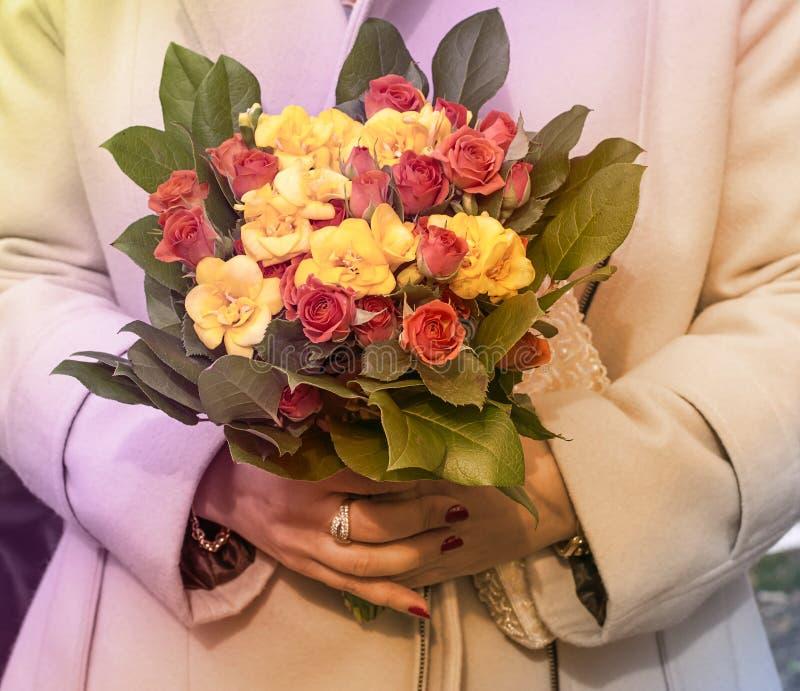 Χέρια γυναικών που κρατούν μια ανθοδέσμη των φυσικών λουλουδιών στοκ εικόνες