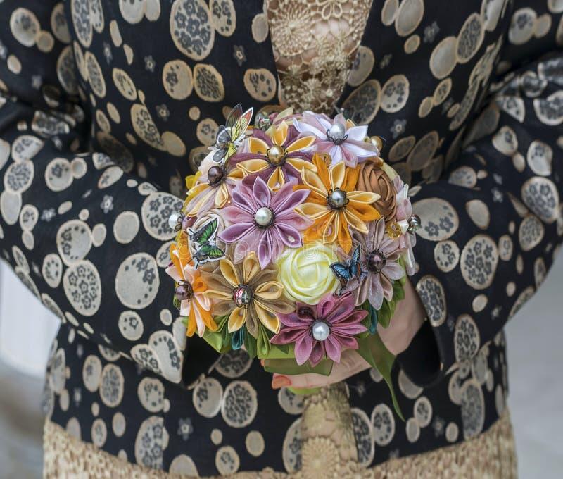 Χέρια γυναικών που κρατούν μια χειροποίητη ανθοδέσμη των τεχνητών λουλουδιών στοκ εικόνα