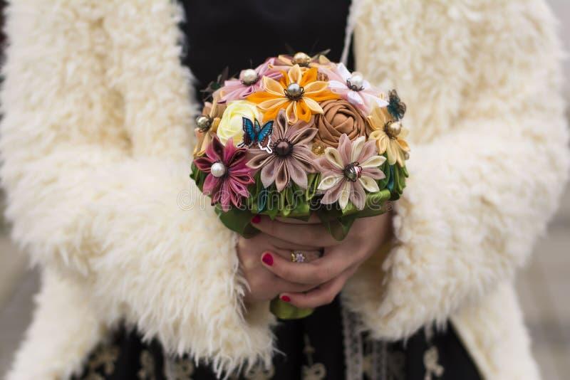 Χέρια γυναικών που κρατούν μια χειροποίητη ανθοδέσμη των τεχνητών λουλουδιών στοκ εικόνα με δικαίωμα ελεύθερης χρήσης