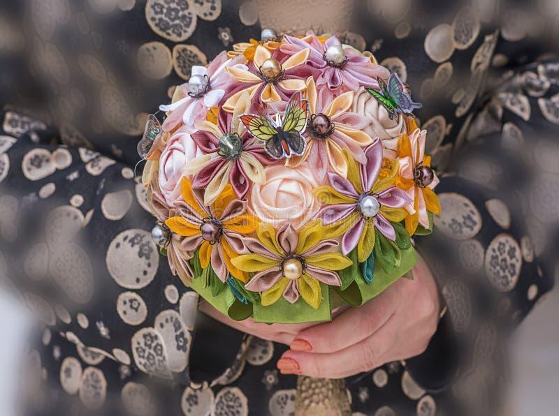 Χέρια γυναικών που κρατούν μια χειροποίητη ανθοδέσμη των τεχνητών λουλουδιών στοκ φωτογραφίες