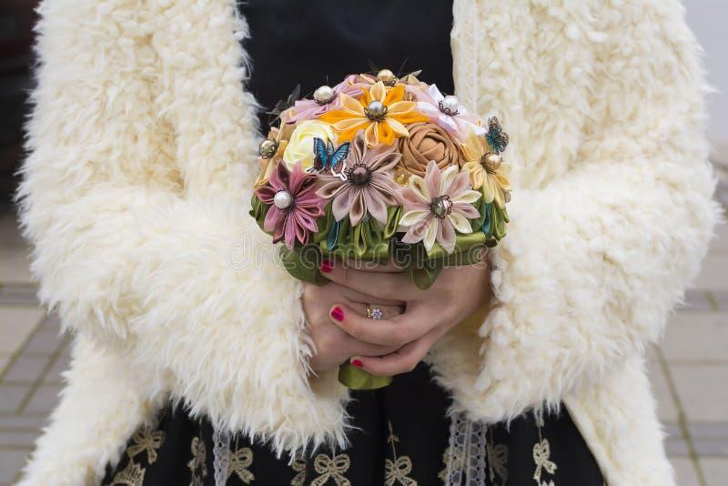 Χέρια γυναικών που κρατούν μια χειροποίητη ανθοδέσμη των τεχνητών λουλουδιών στοκ φωτογραφία με δικαίωμα ελεύθερης χρήσης