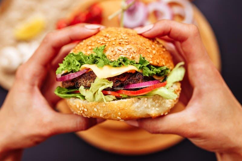 Χέρια γυναικών που κρατούν τα φρέσκα εύγευστα burgers με τη γαλλική σαλάτα, τυρί στην ξύλινη τοπ άποψη επιτραπέζιου υποβάθρου στοκ φωτογραφία