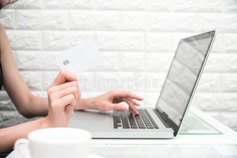 Χέρια γυναικών που κρατούν την πιστωτική κάρτα για on-line να ψωνίσει ή να διατάξει στοκ φωτογραφίες