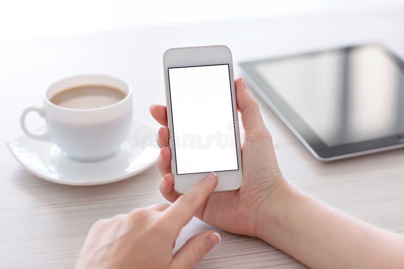 Χέρια γυναικών που κρατούν το άσπρο τηλέφωνο με την οθόνη επάνω από το τ στοκ εικόνα