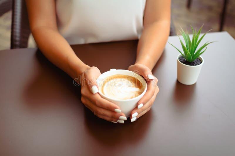 Χέρια γυναικών που κρατούν το cappucino ή latte την τέχνη στοκ φωτογραφία