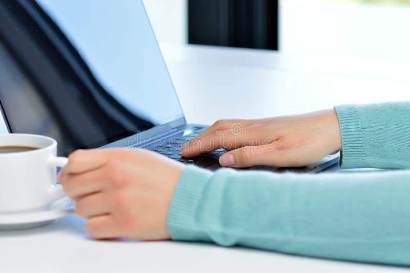 Χέρια γυναικών που λειτουργούν με ένα lap-top σε έναν πίνακα καφετεριών στοκ φωτογραφίες