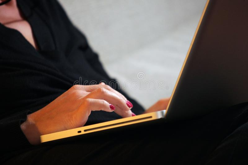 Χέρια γυναικών που λειτουργούν στο lap-top μέχρι αργά στοκ εικόνα με δικαίωμα ελεύθερης χρήσης
