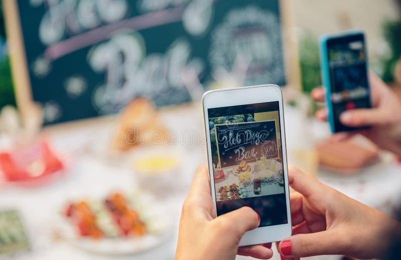 Χέρια γυναικών που παίρνουν τη φωτογραφία στον πίνακα με τα τρόφιμα στοκ φωτογραφίες με δικαίωμα ελεύθερης χρήσης