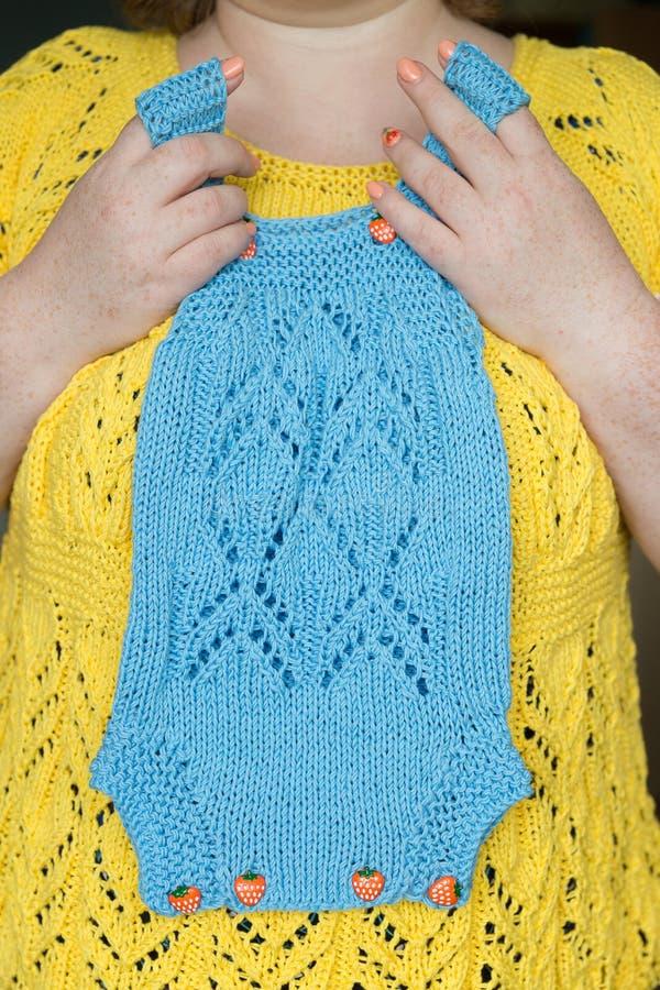 Χέρια γυναικών που πιέζονται ήπια στο πλεκτό στήθος μπλε jumpsuit στοκ φωτογραφία με δικαίωμα ελεύθερης χρήσης