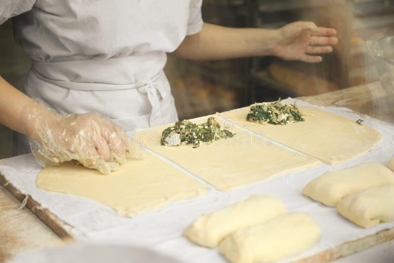 Χέρια γυναικών που προετοιμάζουν τις πίτες από την ακατέργαστη ζύμη στοκ εικόνες με δικαίωμα ελεύθερης χρήσης