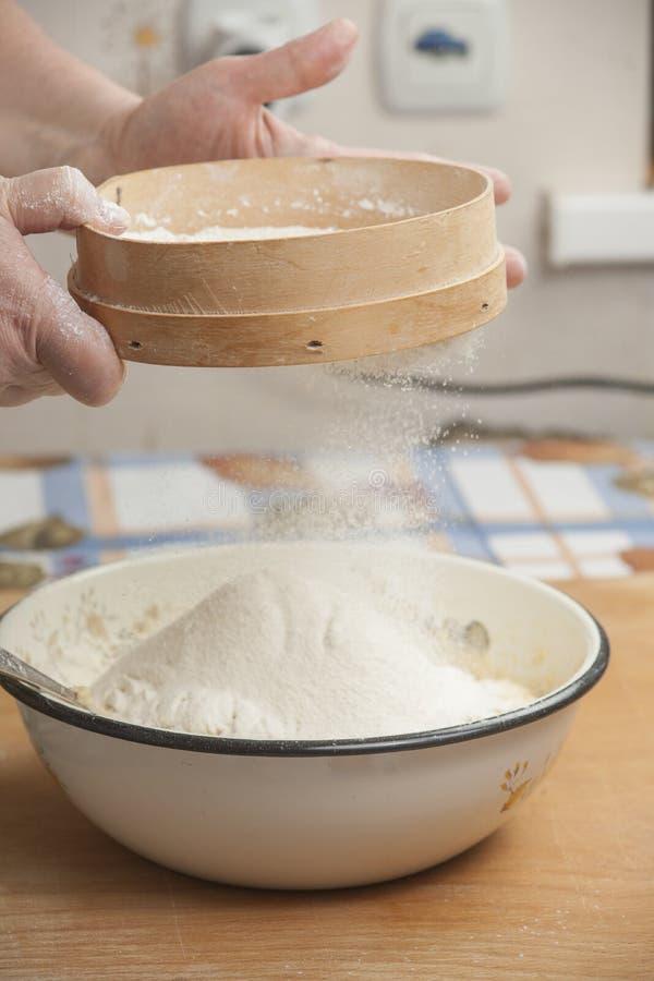 Χέρια γυναικών που προετοιμάζουν το αλεύρι πρίν ψήνει την πίτα στοκ φωτογραφίες