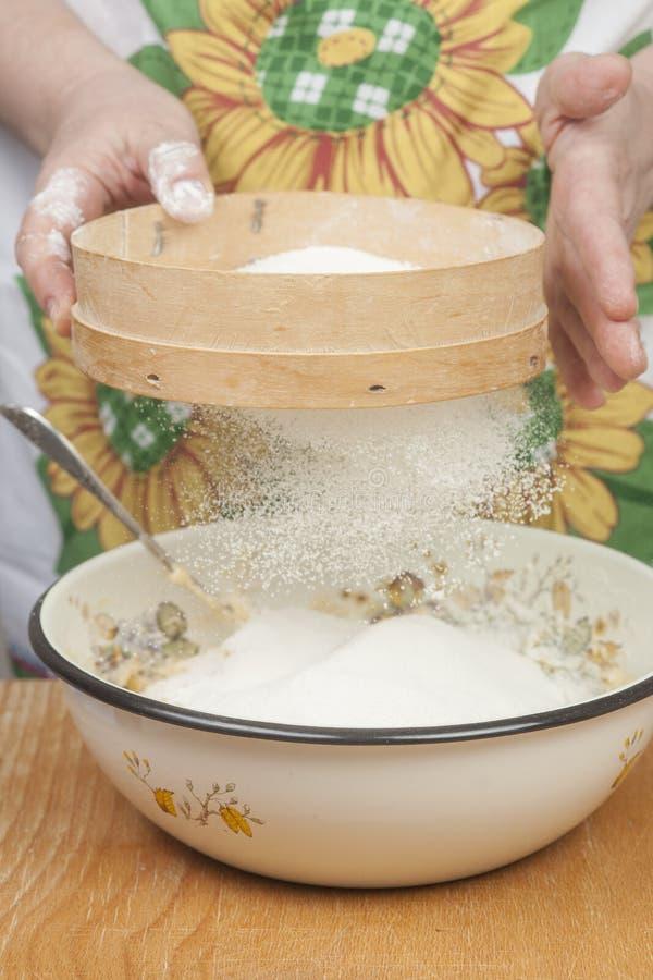 Χέρια γυναικών που προετοιμάζουν το αλεύρι πρίν ψήνει την πίτα στοκ φωτογραφία με δικαίωμα ελεύθερης χρήσης