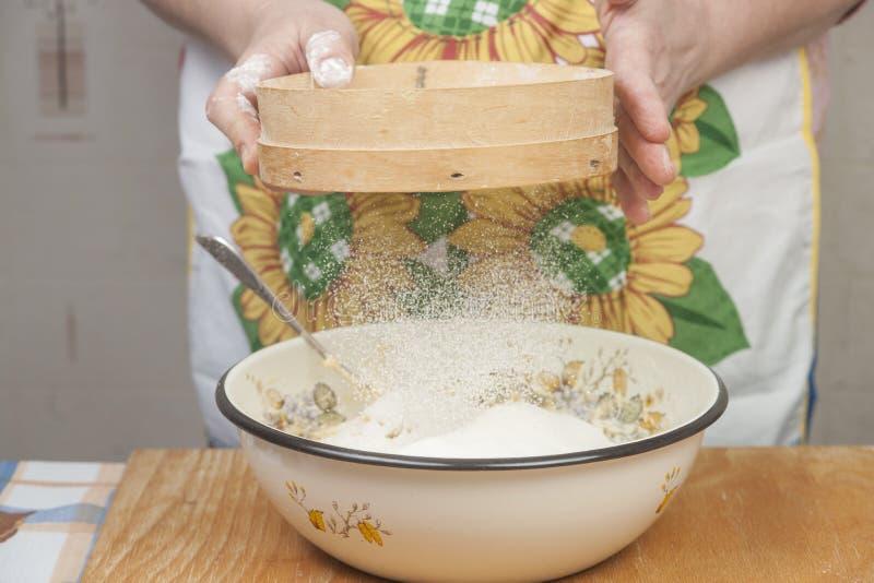Χέρια γυναικών που προετοιμάζουν το αλεύρι πρίν ψήνει την πίτα στοκ φωτογραφίες με δικαίωμα ελεύθερης χρήσης