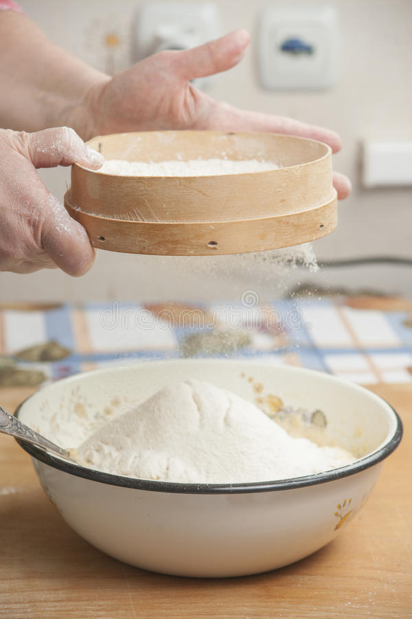 Χέρια γυναικών που προετοιμάζουν το αλεύρι πρίν ψήνει την πίτα στοκ εικόνες με δικαίωμα ελεύθερης χρήσης