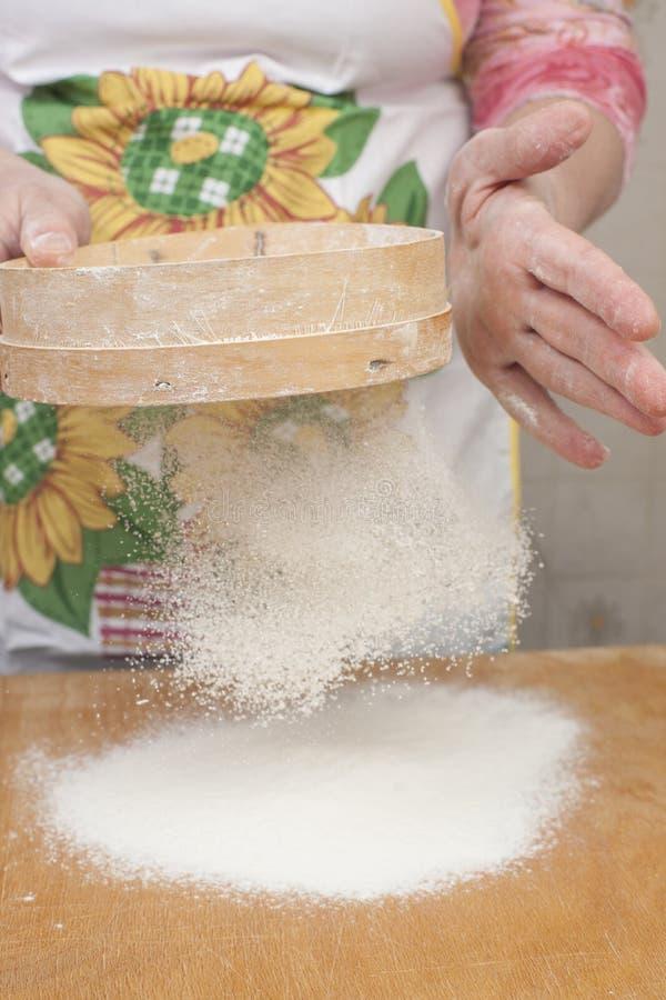 Χέρια γυναικών που προετοιμάζουν το αλεύρι πρίν ψήνει την πίτα στοκ εικόνα